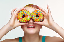Teenager Girl With Unusual Face Art Make-up . Child Looking Through Holes In Donuts.