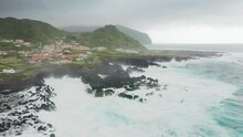 Flores Island, Azores, Portugal. Aerial View Of Pebbled Beach Washed With Foamy Waves Of The Atlantic Ocean. Remote, Charming Settlement Beneath Rocky Green Cliffs. High Quality 4k Footage