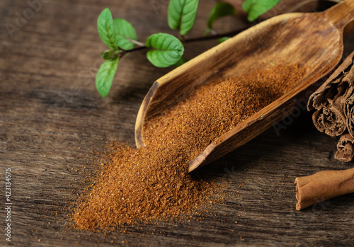 Fototapeta Cinnamon sticks and cinnamon powder in a wooden scoop with mint leaves on the table obraz