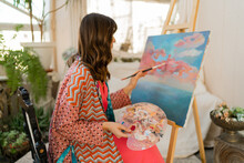 Female Artist Painting On Canvas In Her Art Studio. Wearing Elegant Boho Outfit.