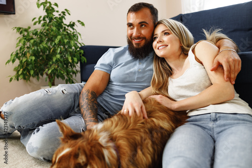 Obraz Young loving couple relaxing in living room with their dog pet - fototapety do salonu