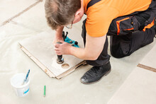 The Tiler Is Using A Diamond Crown To Drill Holes In The Ceramic Tile.