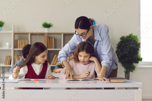 Obraz na płótnie School teacher helping student in class pointing out mistake in child's essay and giving advice on how to correct and improve it