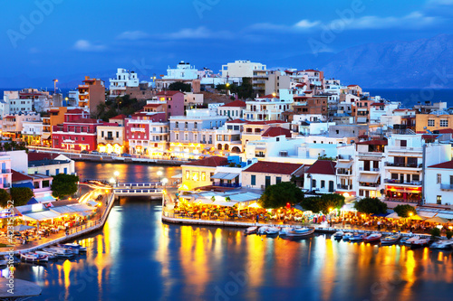 Fototapety, obrazy: Beautiful southern town of Agios Nikolaos at summer evening. Boats swing on the water of the lake Voulismeni at the pier with evening lights. Crete Island. Greece