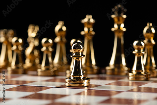 Golden chess figures standing on chessboard Fototapet