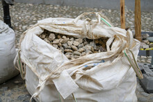 White Bags Of Crushed Stones Are In A Row, Building Material In The Package. Stones To Repair The Road. A Pile Of Cobblestones And Pebbles In Big Bag For Transportation.