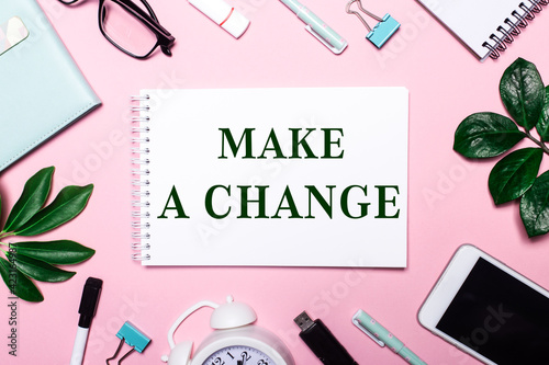 Obraz na plátne MAKE A CHANGE is written in a white notebook on a pink background surrounded by business accessories and green leaves
