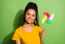 Photo Of Funny Charming Dark Skin Lady Dressed Yellow T-shirt Hiding Pinwheel Toy Isolated Green Color Background