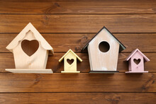 Collection Of Handmade Bird Houses On Wooden Background, Flat Lay
