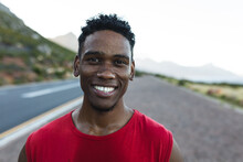 Portrait Of Fit African American Man Exercising Outdoors On A Coastal Road Smiling To Camera