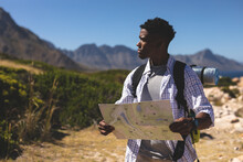 African American Man Exercising Outdoors Reading Map In Countryside On A Mountain
