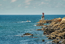 Lighthouse On The Rocky Shore Of The Ocean