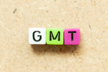 Color Alphabet Letter Block In Word GMT (abbreviation Of Greenwich Mean Time) On Wood Background