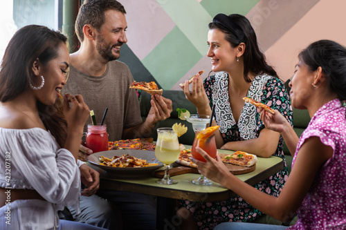 Group of young multiethnic friends eating, talking and laughing in restaurant or Wallpaper Mural