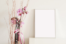 Empty Vertical Picture Frame With Beautiful Pink Flowers On White Wall Background