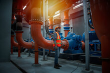 Male Worker Checking Valve On Water Pump In Plant Room Background.