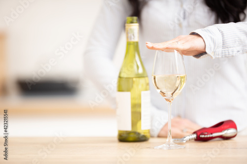 Fototapeta Woman holding hand above the glass of white wine to express she had enough obraz