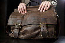 Teachers Female Hands Hold On To An Antique Brown Leather Briefcase.