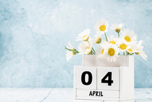 Cube Calendar For April Decorated With Daisy Flowers Over Blue With Copy Space