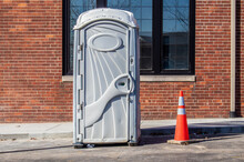 Gray Plastic Portable Bathroom Sitting In Parking Lot In Front Of Brick Building - Female Symbol On Door And Contruction Cone Next To It