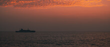 A Ship Traveling In The Horizon, Glorious Colorful Sunset Skies, Calm Low Tide Ocean Shore, View From The Famous Galle Fort.