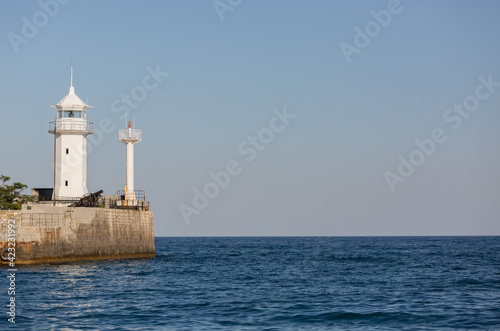 White lighthouse on the beach on a clear sunny day Fototapet