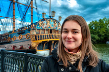 A Woman Smiles Next To The Stern Of The Ship Against The Backdrop Of Epic Clouds