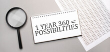 1 Year 365 Possibilities Sign In White Paper Notepad And Magnifying Glass On The Grey Background