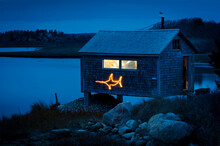 Fishing Shack On Martha's Vineyard Decorated For Christmas With Fish Light. This Small Shack Is Used By Fisherman To Work On The Fresh Catch Of Scallops From The Day.