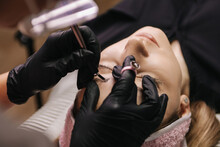 Eyebrow Microblading. A Master In A Transparent Mask On His Face And Black Gloves Holds A Handpiece With A Shading Needle Over The Eyebrow Of The Model.