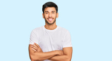 Young Handsome Man Wearing Casual White Tshirt Happy Face Smiling With Crossed Arms Looking At The Camera. Positive Person.