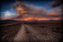 A Rocky And Dusty Road Winds Its Way Down The High Desert In SW Bolivia Leading Your Eyes To A Dramatic Sunset.