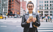 Half Length Of Happy Female In Leather Jacket And Eyewear Smiling At Camera While Waiting For Sms Answer On Modern Mobile Phone,cheerful Hipster Girl With Textbook And Cellular Posing At Urban Setting