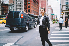 Happy Chinese Woman With Education Sketchbook Gesturing For Catch Cab Transport And Get To Destination In Urban City, Cheerful Hipster Girl In Optical Spectacles Waving At Street With Traffic