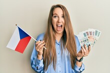 Young Blonde Woman Holding Czech Republic Flag And Koruna Banknotes Celebrating Crazy And Amazed For Success With Open Eyes Screaming Excited.