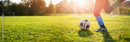 Obraz Child playing football on the field with gates. - fototapety do salonu