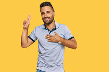 Handsome Man With Beard Wearing Casual Clothes Smiling Swearing With Hand On Chest And Fingers Up, Making A Loyalty Promise Oath