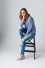 Cute Young Caucasian Pretty Woman With Long Hair In Blue Shirt And Ripped Jeans