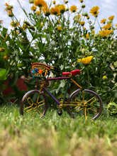 Beautiful Handmade Miniature Bicycle Placed On Grass With Flowers In The Background.