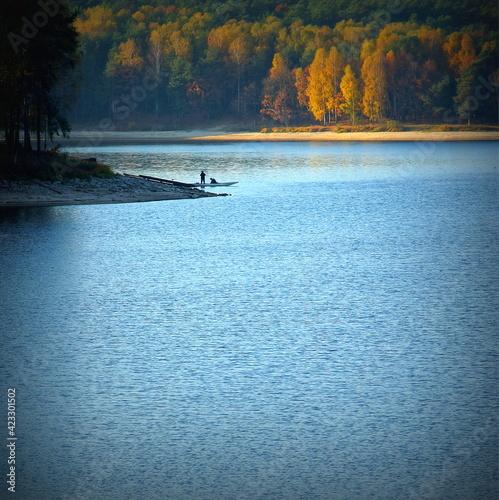 łódź z wędkarzem w jesiennych kolorach oświetlonych słońcem