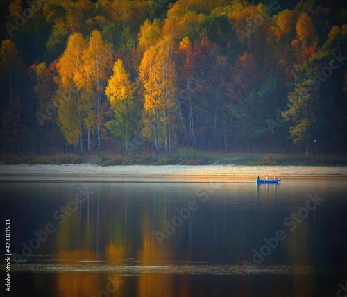 Fototapeta łódź z turystami w jesiennych kolorach oświetlonych słońcem obraz