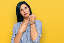 Young Caucasian Woman Wearing Casual Clothes In Hurry Pointing To Watch Time, Impatience, Looking At The Camera With Relaxed Expression