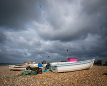 Fishing Boats On The Stony Shore At Seaford Beach With Storm Clouds Overhead.