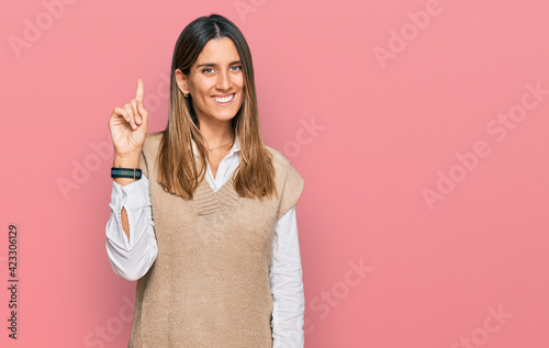 Fototapeta Young woman wearing casual clothes showing and pointing up with finger number one while smiling confident and happy. obraz