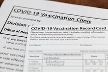 Close Up Isolated Image Of A COVID 19 Vaccination Record Card On A Wooden Desk. The Card Details The Date, Type And The Dose Number Of Administred Vaccine And Given To Every Person For Record.
