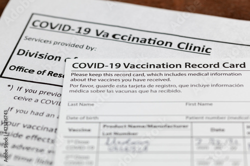 Fotografie, Tablou Close up isolated image of a COVID 19 vaccination record card on a wooden desk