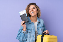 Young Blonde Woman With Curly Hair Isolated On Purple Background In Vacation With Suitcase And Passport