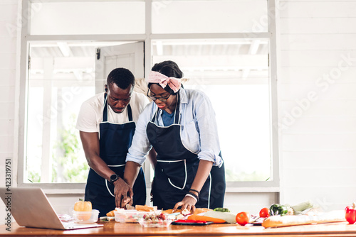 Papel de parede Portrait of love african american couple having fun cooking food together with f