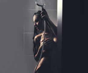 Sensual young naked woman with beautiful nude body in bath under water taking shower. Sexy girl bathtub.