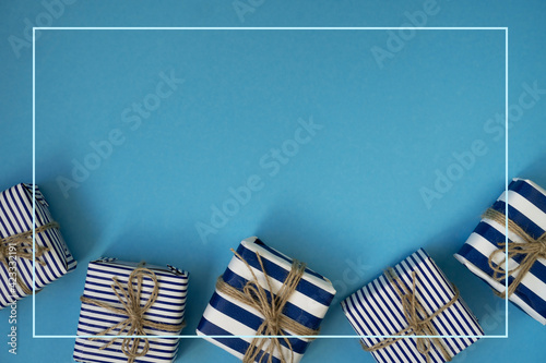 Fototapeta Holiday gifts decorated with striped paper on a blue background obraz